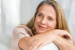 Mature woman thinking. Smiling senior woman sitting on couch and thinking about her new idea. Portrait of pensive lady relaxing at home and looking away. Closeup stock photos