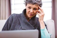 Mature woman thinking while using laptop Stock Image