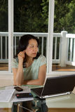 Mature woman thinking while working at home Stock Images