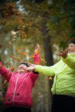 Mature woman throwing leaves into the air in an autumn park. Mid shot royalty free stock photography