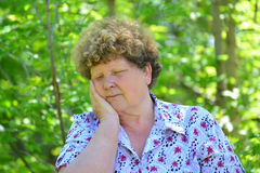 Mature woman with toothache in the summer park Stock Photography