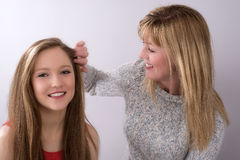 Mature woman touching hair of a teenage girl Royalty Free Stock Photo
