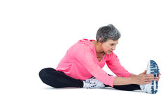 Mature woman touching toes while exercising Stock Images