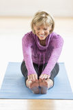 Mature Woman Touching Toes On Yoga Mat. Happy mature woman touching toes while sitting on yoga mat at home Stock Photos