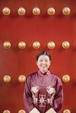 Mature woman in traditional clothes standing next to traditional Chinese door Stock Images