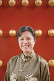 Mature woman in traditional clothes standing next to traditional Chinese door Stock Image