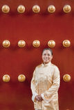 Mature woman in traditional clothes standing next to traditional Chinese door Stock Photography