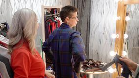 Mature woman trying clothes front mirror in clothing shop. Adult woman choosing new clothes together friends in boutique stock video footage