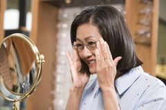 Mature Woman Trying Out Glasses Royalty Free Stock Images