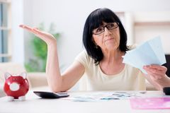 The mature woman trying to reconcile her bills stock image