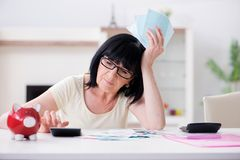 The mature woman trying to reconcile her bills. Mature woman trying to reconcile her bills Royalty Free Stock Image