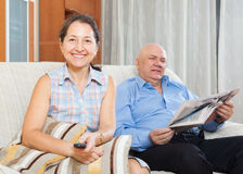 Mature woman with TV remote against  man with newspaper Royalty Free Stock Photography