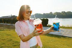Mature woman with two drinks in her hands. Green recreation and entertainment area near the river, copy space, golden hour stock images