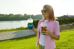 Mature woman with two drinks in her hands. Green recreation and entertainment area near the river, copy space. stock image