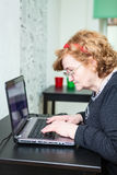 Mature woman typing on laptop keyboard Royalty Free Stock Photography