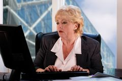 Mature woman typing in office Royalty Free Stock Photo