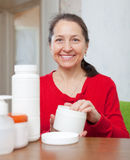 Mature woman uses cosmetic cream Stock Photography