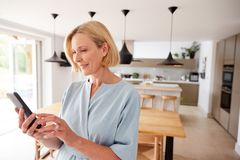 Free Mature Woman Using App On Mobile Phone To Control Central Heating Temperature In House Royalty Free Stock Photo - 163726805
