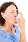Mature woman using asthma inhaler Stock Photos