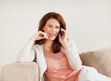 Mature woman using cellphone relaxing on couch Stock Photos