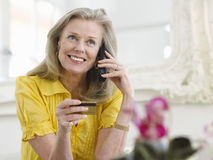 Mature Woman Using Credit Card And Phone Stock Images
