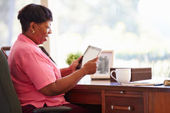 Mature Woman Using Digital Tablet On Desk At Home Stock Images