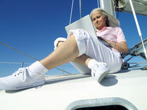 Mature woman using laptop computer on boat, low angle view Royalty Free Stock Photo