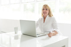 Mature woman using laptop at home Stock Images