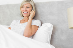 Mature woman using mobile phone in bed Royalty Free Stock Images