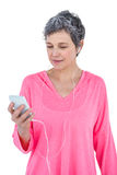 Mature woman using mobile phone while listening music Stock Images