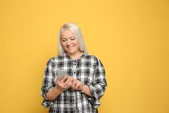 Mature woman using mobile phone. On color background stock photos