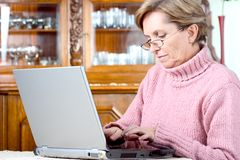 Mature woman using notebook. Mature woman typing on a notebook computer Royalty Free Stock Photos