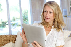 Mature woman using tablet stock photography