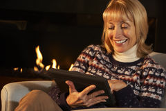 Mature woman using tablet in front of fire at home Royalty Free Stock Photos
