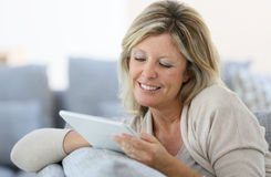 Mature woman using tablet on sofa Royalty Free Stock Image