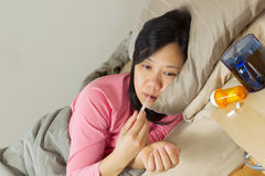 Mature Woman using Thermometer while lying in bed sick Royalty Free Stock Photos