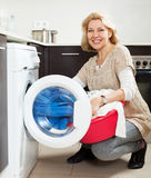 Mature woman using washing machine at home Royalty Free Stock Photos