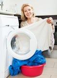 Mature woman using washing machine Royalty Free Stock Photo