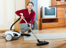 Mature woman with vacuum cleaner on parquet floor Stock Photography