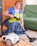 Mature woman vacuuming Stock Photo