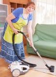 Mature woman vacuuming Stock Image
