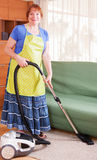 Mature woman vacuuming Stock Image