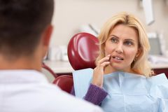 Mature woman visiting dentist at the clinic. Gorgeous mature women talking to her dentist before receiving medical treatment for her toothache. Beautiful female royalty free stock images