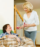 Mature woman visiting  sick elderly friend and giving her a linc Royalty Free Stock Image