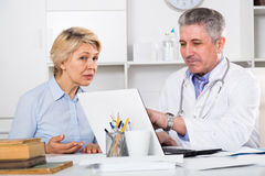 Mature woman visits doctor. Mature women visits doctor in hospital for survey and check of your health stock photos