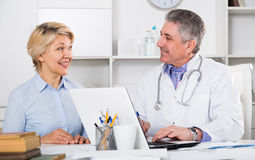 Mature woman visits doctor. Mature women visits doctor to medical office for planned inspection of health royalty free stock photo