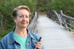 Mature woman waiting your call. Dressing in a denim jacket, a senior Caucasian lady is standing by river bridge, holding a mobile Royalty Free Stock Photo