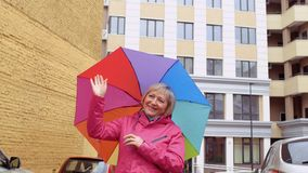 Senior woman with colorful umbrells meet someone at the street. Mature woman walk with colorful umbrella stand outdoors and enjoys view around. Senior woman wave stock video footage