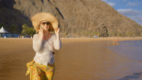 Mature woman on a walk on the sandy beach of a tropical island. A woman walks along the beach at sunset, breathing the sea air and talking on the phone with stock video
