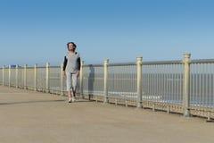 Mature woman walking by the beach. Mature woman walking casually by the beach Stock Photo